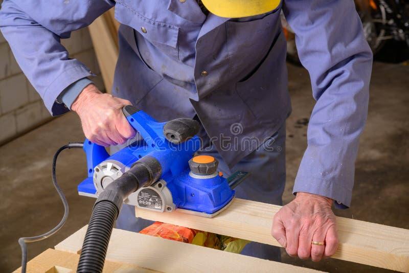Een mens werkt met elektrische planer stock foto's