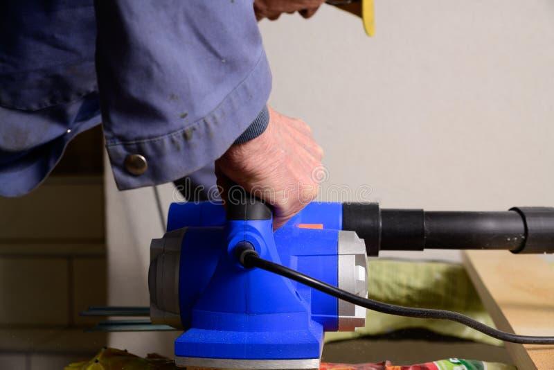 Een mens werkt met elektrische planer royalty-vrije stock foto