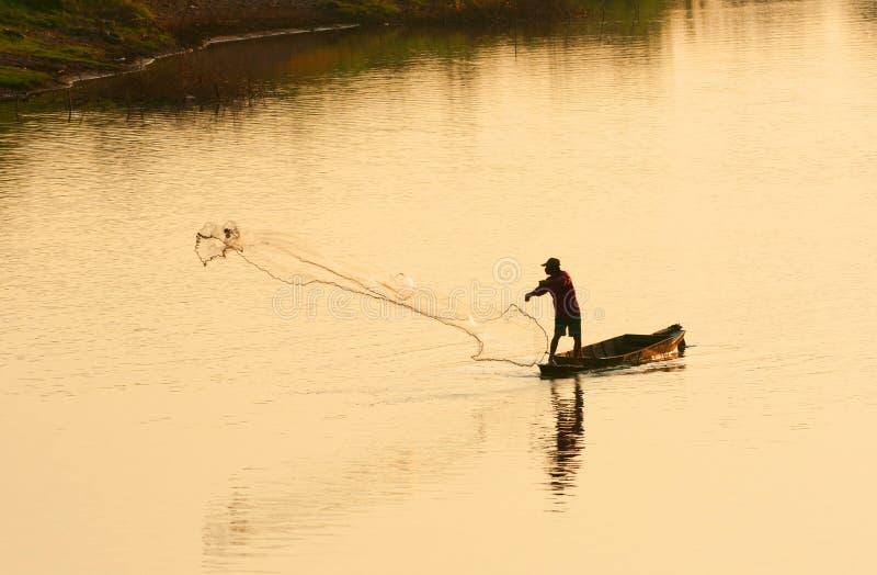 Een mens werpt visnet in avond stock fotografie