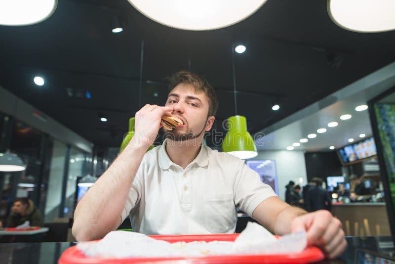 Een mens zit bij de lijst in een koffie en eet een heerlijke sandwich Snack bij het snel voedselrestaurant royalty-vrije stock foto