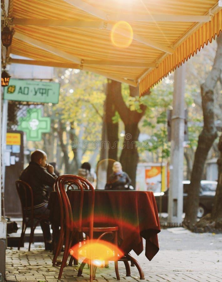 Een mens zit in de recente dagzon op de straten van Odessa, de Oekraïne royalty-vrije stock foto