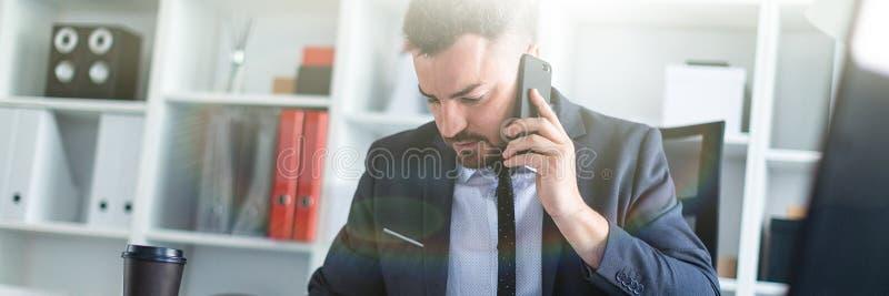 Een mens zit in het bureau bij de lijst, spreekt op de telefoon en knipt door documenten weg royalty-vrije stock foto