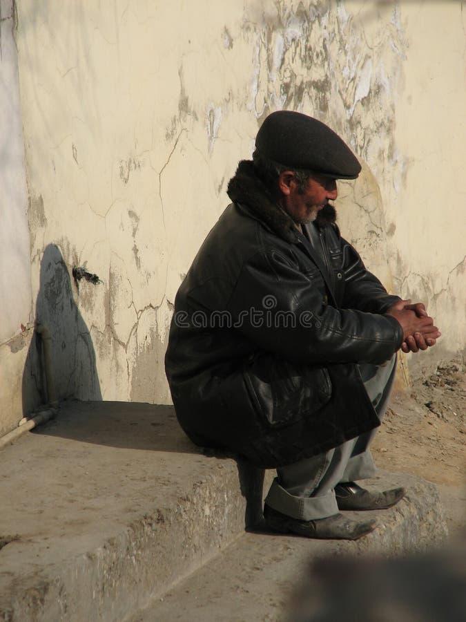 Een mens zit op de zonnige straten van Baku, Azerbeidzjan stock foto