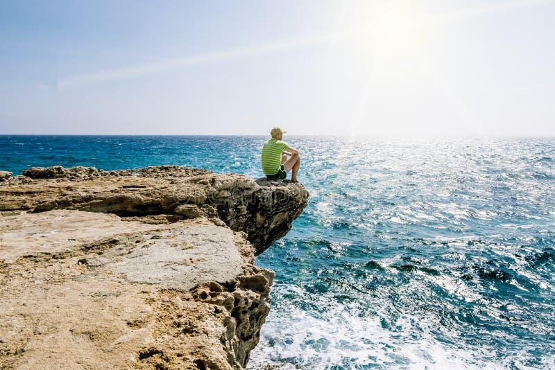 Een mens zit op een richel van rots boven het overzees bij Kaap Greco stock foto
