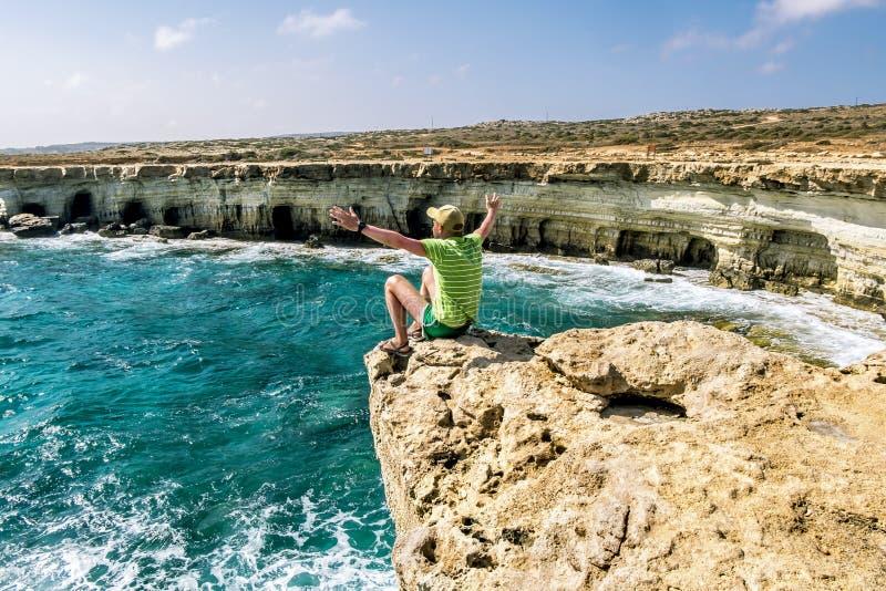 Een mens zit op een richel van rots boven het overzees bij Kaap Greco Cypr stock afbeelding