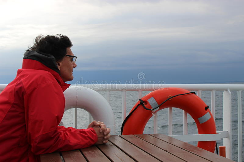 Een mens zit op het dek van een kleine veerboot in Noorwegen, die de Noordzee bekijken stock afbeeldingen