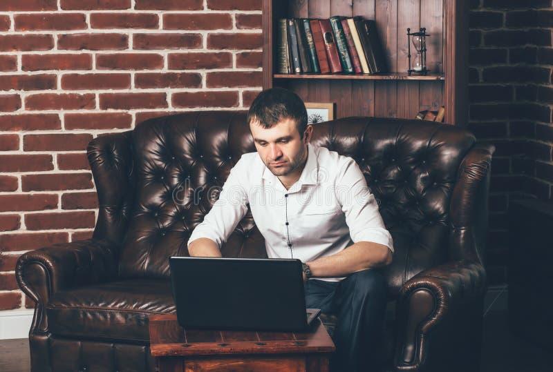 Een mens zit op een luxueuze bank en werkt achter laptop in zijn bureau aan de achtergrond van het boekenrek stock fotografie
