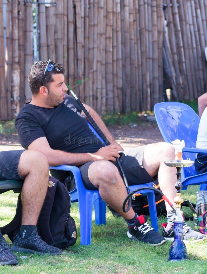Een mens zit op een stoel en het roken van een waterpijp op rust in Tiberias, Israël stock foto