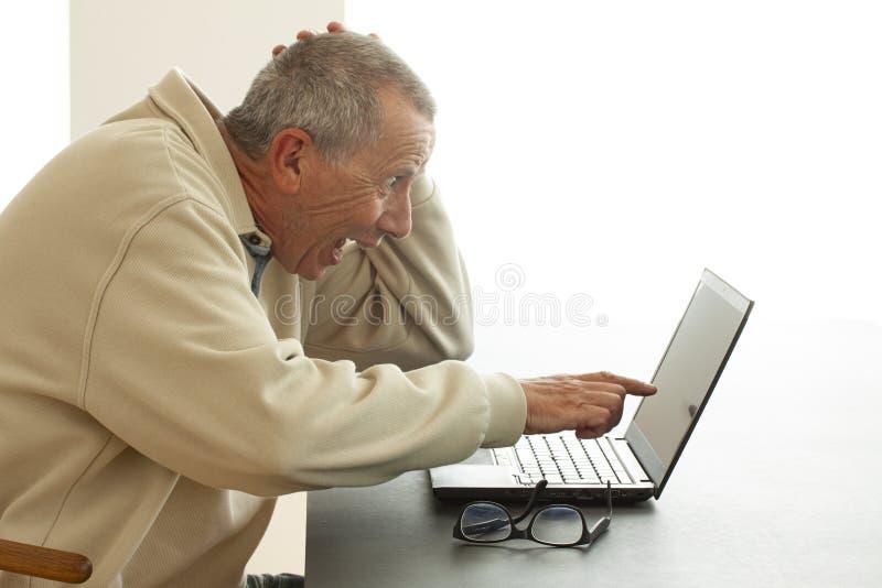 Een mens zit zeer verrast het kijken met open mond aangezien hij aan het scherm van een notitieboekjecomputer richt Hij leest of  stock foto's