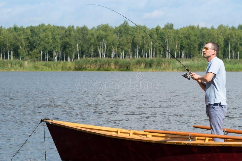 Een mens in zonnebril op een boot vist met behulp van het spinnen in mooi weer op het meer, actieve recreatie stock fotografie