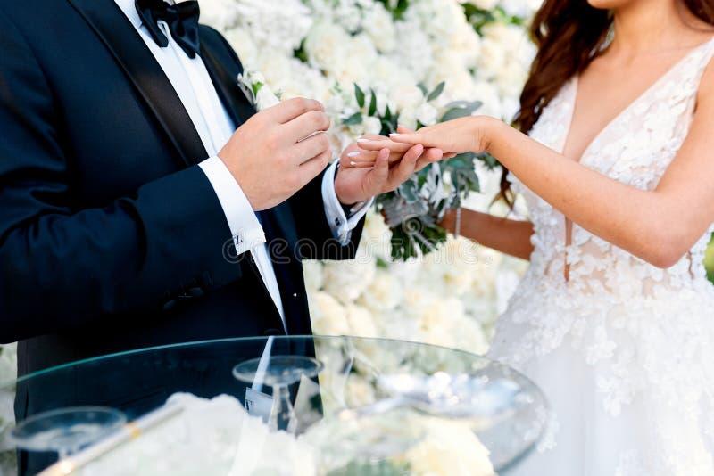 Een mens in een zwart kostuum zet een ring op de vinger van zijn bruid royalty-vrije stock fotografie