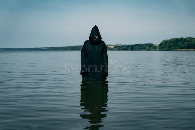Een mens in een zwarte robe met een kap bevindt zich in de loop van de dag in de rivier Hij bekijkt mysteriously het water royalty-vrije stock afbeeldingen