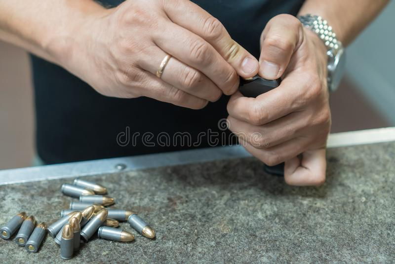 Een mens in een zwarte T-shirt belast de pistoolhouder met 9 19 patronen stock fotografie