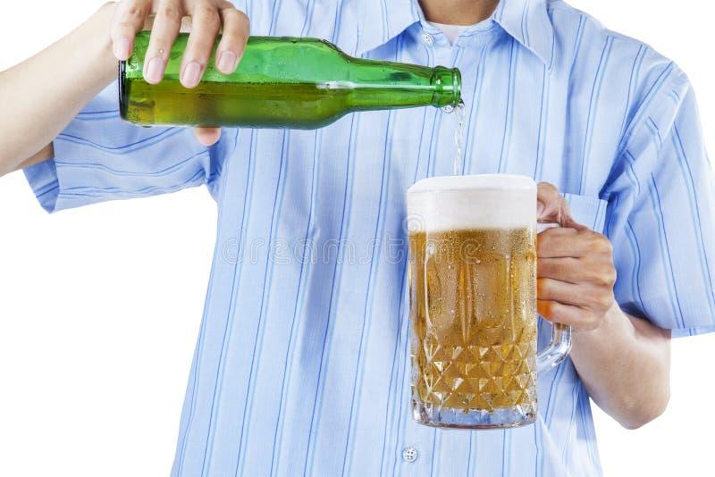 Een mensen gietend bier in glas stock foto