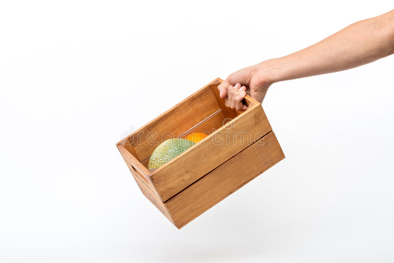 Een mensen` s hand die een houten doos houden die meloenen en sinaasappelen bevatten royalty-vrije stock afbeelding