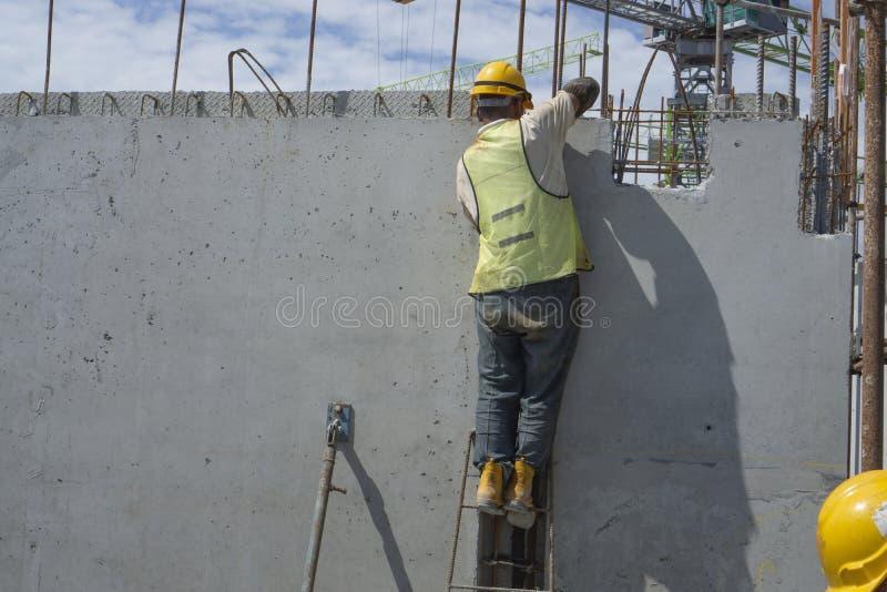 Een mensenbouwer installeert geprefabriceerde concrete muurstructuur met staalbar op hoogste vloer van de bouw, oppassend voor or stock foto