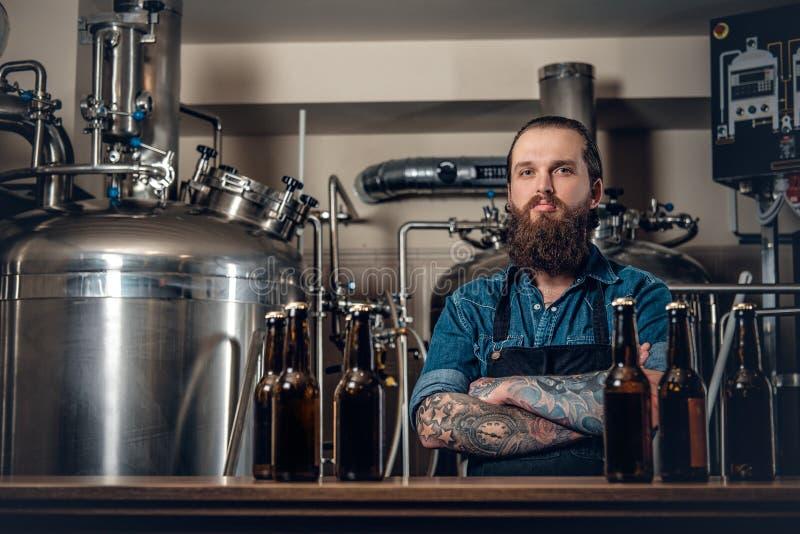 Een mensenfabrikant die bier in microbrewery voorstellen royalty-vrije stock afbeelding