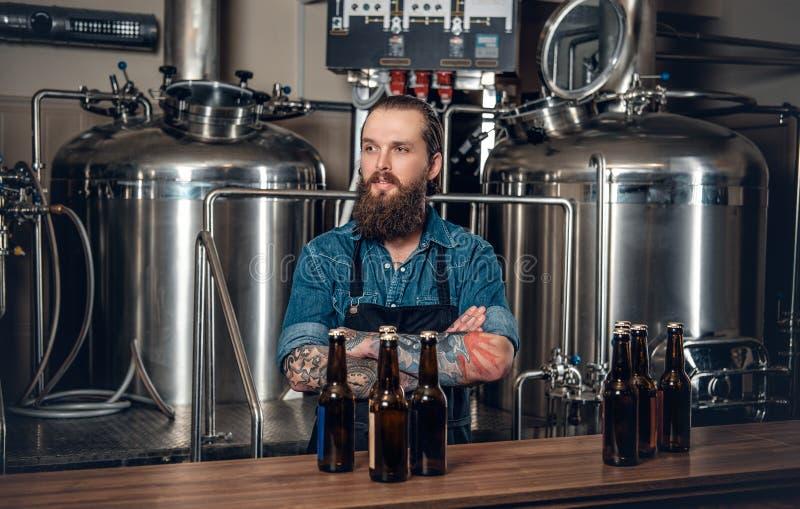 Een mensenfabrikant die bier in microbrewery voorstellen royalty-vrije stock afbeeldingen