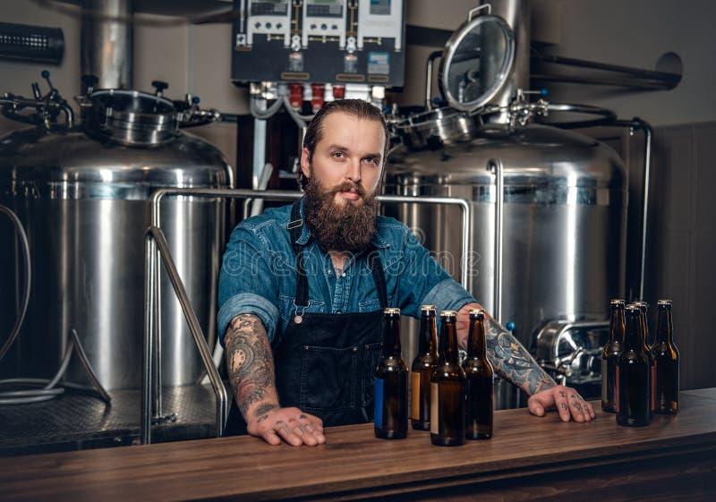Een mensenfabrikant die bier in microbrewery voorstellen stock foto