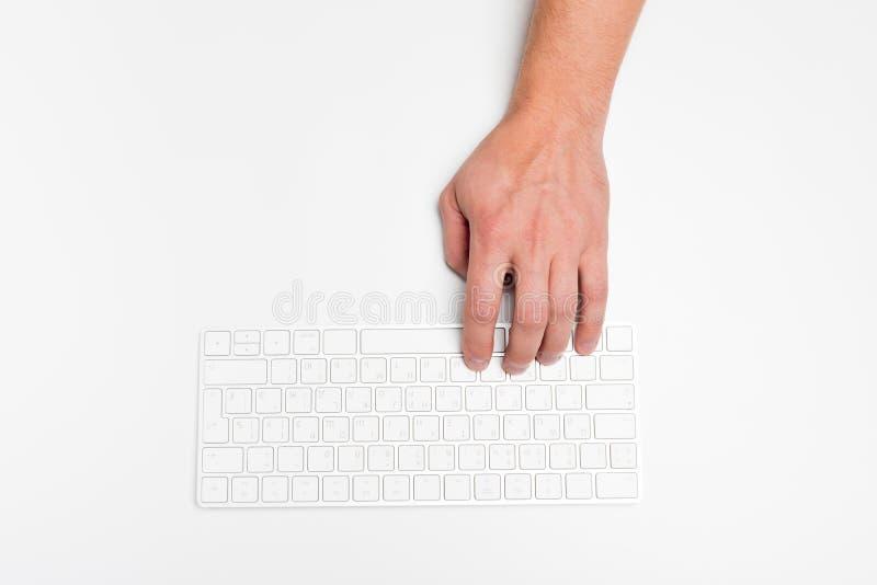 Een mensenhand die een draadloos die toetsenbord gebruiken op wit wordt geïsoleerd stock foto's