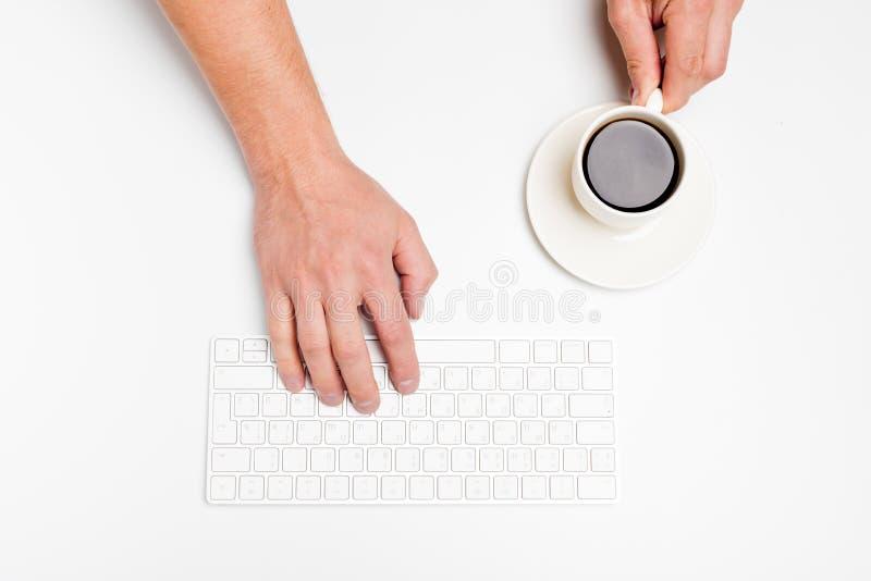 Een mensenhand houdt een draadloze toetsenbord en koffiekop op wit stock afbeeldingen