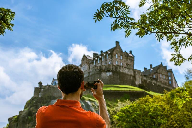 Een mensentoerist die beeld van het Kasteel van Edinburgh in de lentetijd nemen stock foto