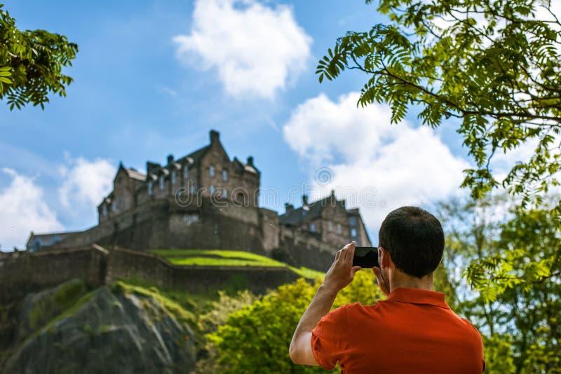Een mensentoerist die beeld van het Kasteel van Edinburgh in de lentetijd nemen stock afbeeldingen