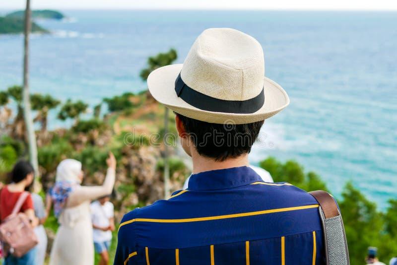 Een mensentoerist met de hoed van Panama kijkt binnen het mooie natuurlijke landschap van het overzees op het hoogste meningspunt stock afbeelding