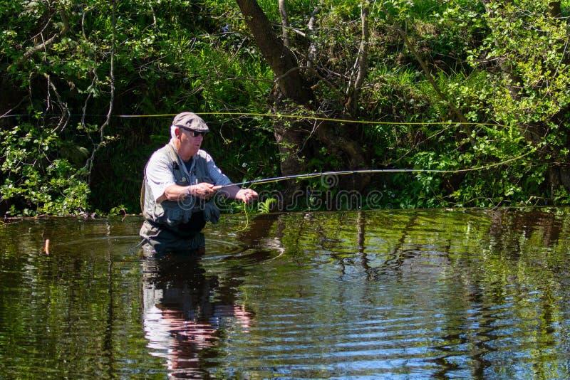 Een Mensenvlieg die op een Rivier vissen stock foto