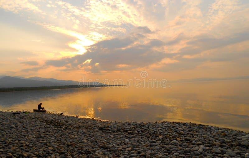 Een mensenzitting alleen op een logboek bij het overschot de rand van een overzees, dageraadstilte op meer royalty-vrije stock foto's