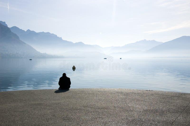 Een mensenzitting bij meer Annecy royalty-vrije stock fotografie