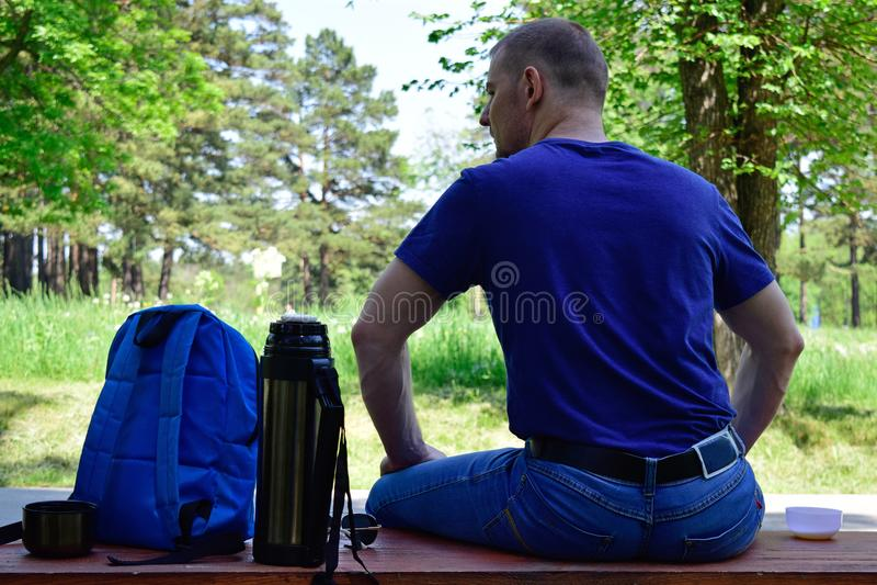 Een mensenzitting in het Park op een bank De mens bewondert aard royalty-vrije stock foto's