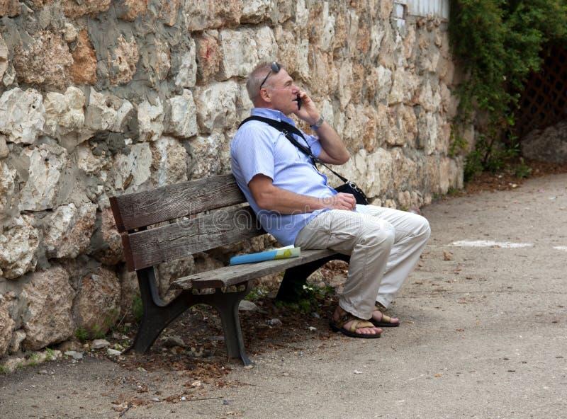 Een mensenzitting op een bank en het spreken op de telefoon royalty-vrije stock foto's