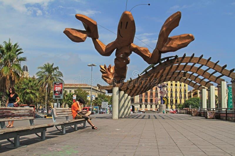 Een mensenzitting op een bank naast een beeldhouwwerk van een reuzezeekreeft op de waterkant in de oude Haven van Barcelona royalty-vrije stock foto