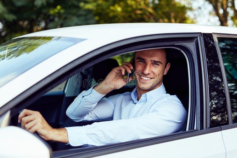 Een mensenzitting in zijn auto en het spreken op de telefoon stock fotografie