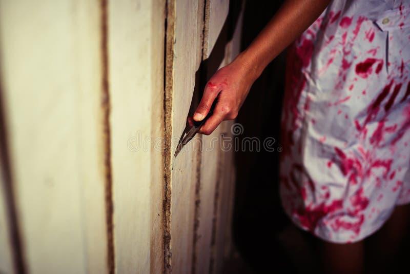 Een mes van de Vrouwenholding met bloed, Halloween-concept stock fotografie