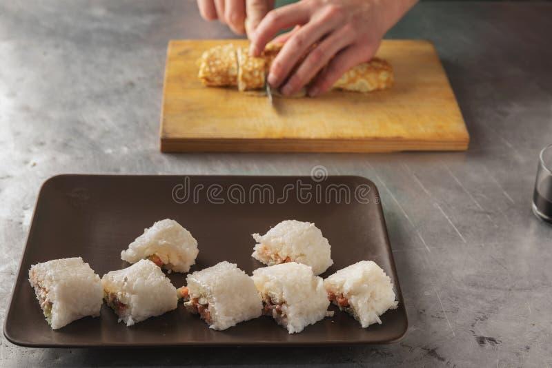 Een mes in zijn hand snijdt een broodje van rijst close-up op een houten raad stock fotografie
