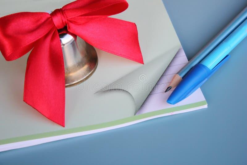 Een metaalklok met een rode boog wordt gevestigd op schoolnotitieboekje naast pen en potlood royalty-vrije stock foto