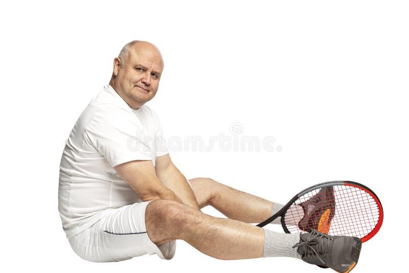 Een midden oude mens zit op de vloer met een tennisracket in zijn handen Ge?soleerd op een witte achtergrond royalty-vrije stock afbeelding