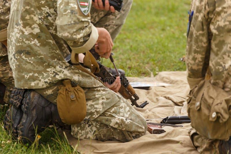 Een militair assembleert een Kalashnikov van het aanvalsgeweer stock afbeelding