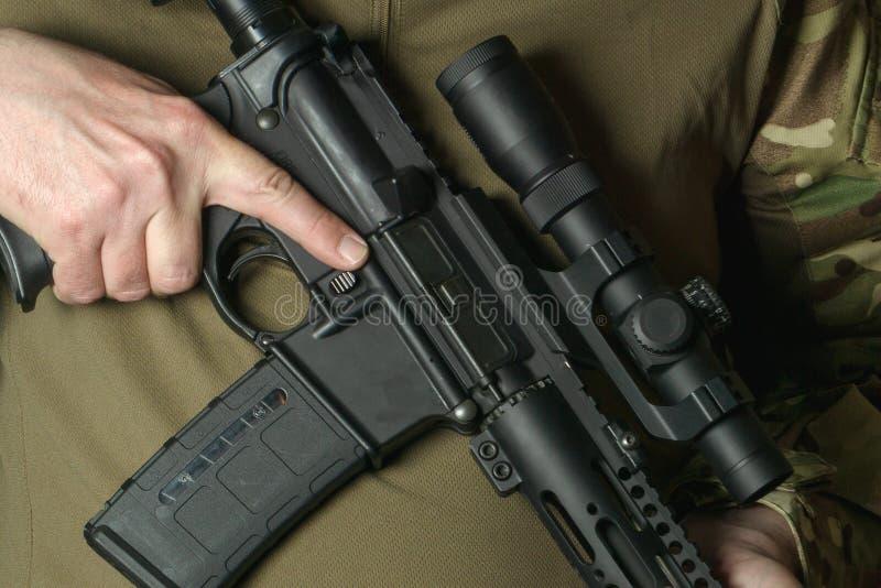 Een militair die een geweer met een telescopisch gezicht houden stock afbeelding