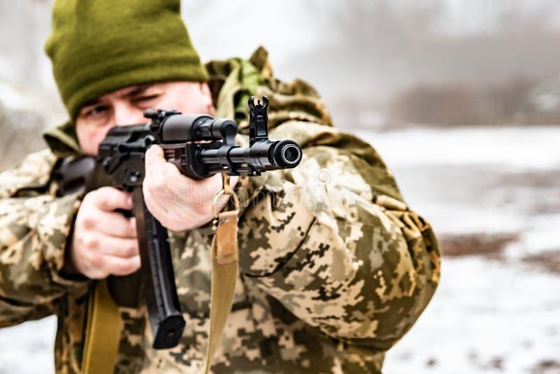 Een militair met een kanon AKM, doelstellingen bij de vijand Vat en snuitmachine dichte omhooggaand royalty-vrije stock fotografie