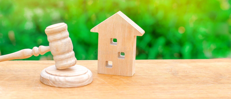 Een miniatuurblokhuis en een hamer van de rechter De veiling om te kopen/verkoopt een huis Gedwongen uitzetting en inbeslagneming royalty-vrije stock foto's