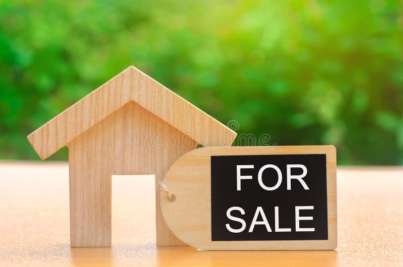 Een miniatuurblokhuis en een inschrijving voor Verkoop Het concept het verkopen van een huis of een flat Bezit voor verkoop betaa royalty-vrije stock afbeeldingen