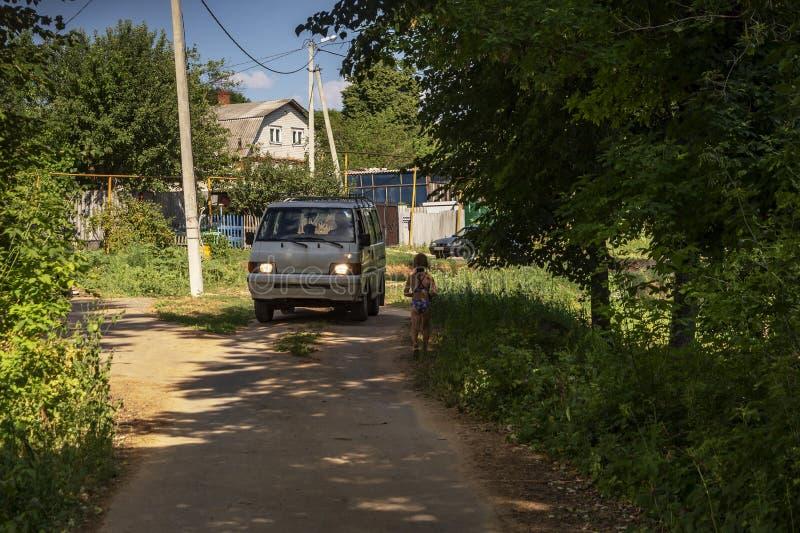 Een minibus die de landweg bewegen dichtbij huis, bomen Een meisje walkin van het strand royalty-vrije stock foto's