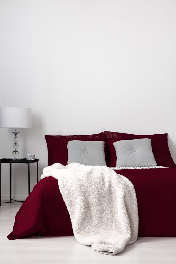 Een minimalistic slaapkamerbinnenland met een bed gekleed in het linnen van Bourgondië, grijze gewatteerde kussens en vanille zac stock afbeeldingen