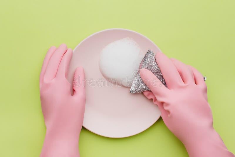 Een minimalistisch het schoonmaken concept, dient roze rubberhandschoenen met in stock foto