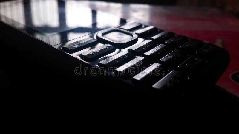 EEN MOBIELE TELEFOON DIE OP LICHT WIJZEN stock foto