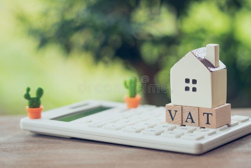 Een modelhuismodel wordt geplaatst op de houten woordbtw als concept van achtergrondbezitsonroerende goederen met exemplaarruimte stock foto