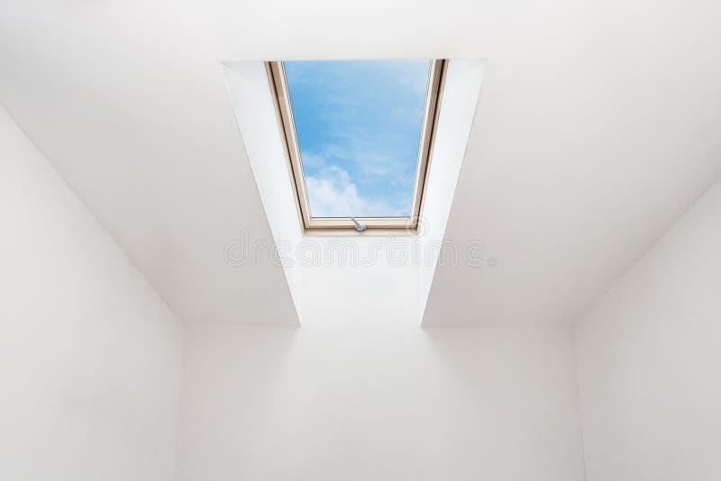 Een modern open dakraammansard venster in een zolderruimte tegen blauwe hemel stock fotografie